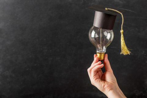 person-holding-light-bulb-with-graduation-cap